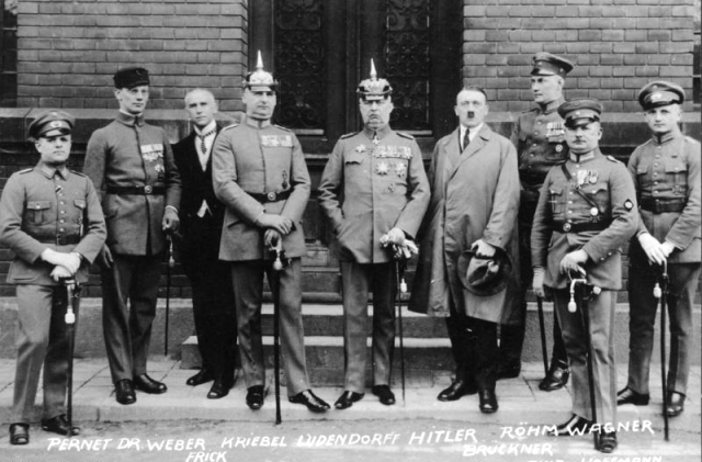From left to right: Pernet, Weber, Frick, Kiebel, Ludendorff, Hitler, Bruckner, Röhm, and Wagner. Note that only two of the defendants (Hitler and Frick) were wearing civilian clothes.